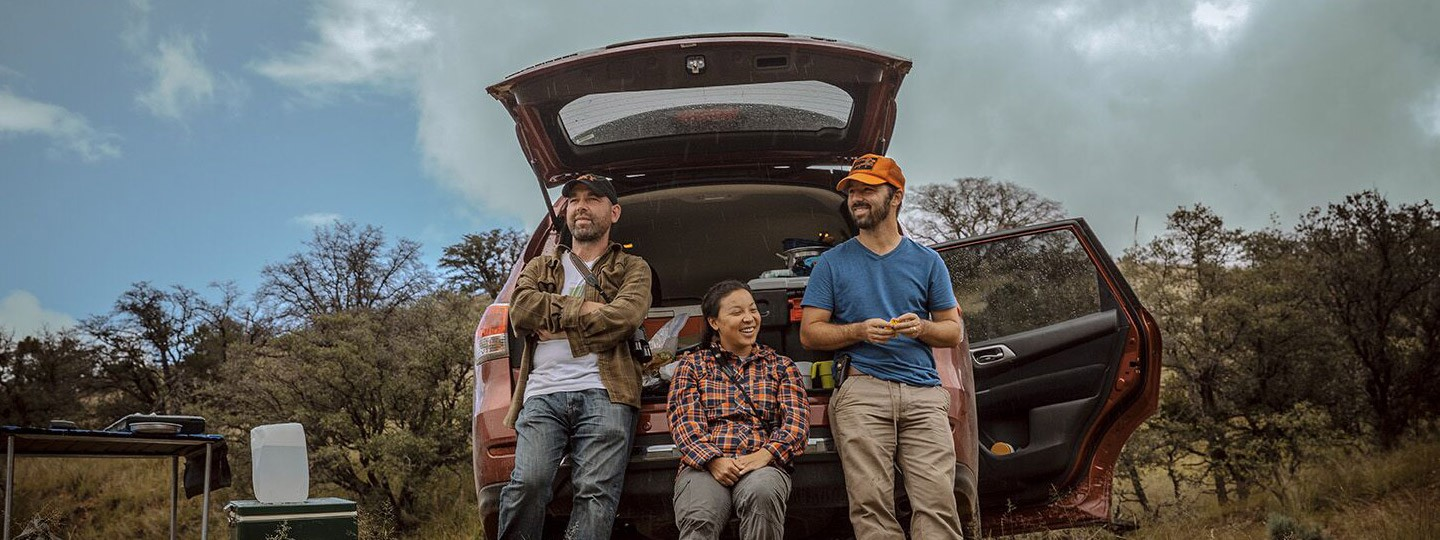 James Maley, Whitney Tsai Nakashima, and John McCormack stand next to a car on a field expedition