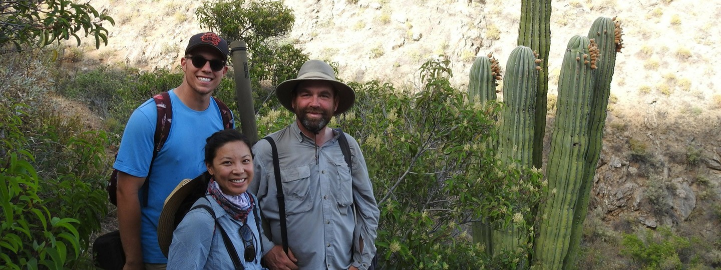 Moore Lab researchers smile surrounded by cacti and other native vegetation on an expedition in Mexico